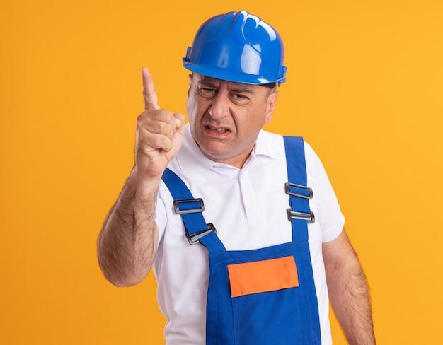 Homem construtor adulto, caucasiano, insatisfeito, com uniforme, aponta para cima na laranja