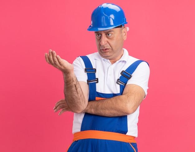 Homem construtor adulto sem noção em uniforme parece e aponta para o lado com a mão isolada na parede rosa