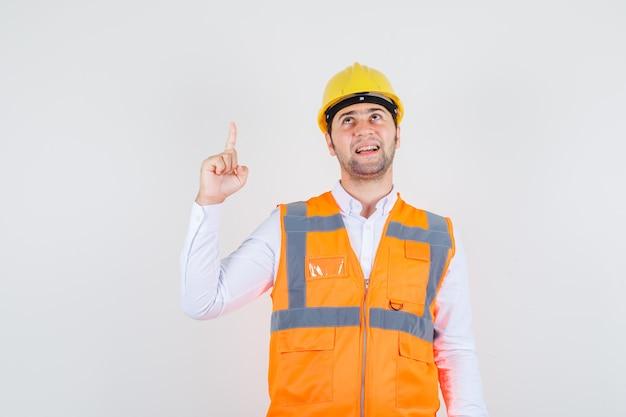 Homem construtor apontando o dedo na camisa, uniforme e parecendo alegre. vista frontal.