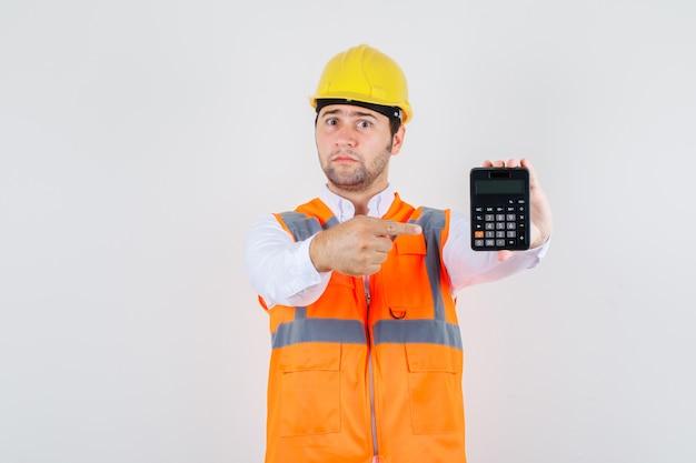 Homem construtor apontando o dedo para a calculadora de camisa, uniforme e olhando ansioso, vista frontal.