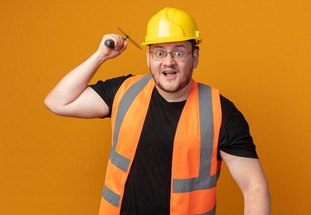 Homem construtor com colete de construção e capacete de segurança balançando uma espátula emocionado e surpreso em pé sobre a laranja