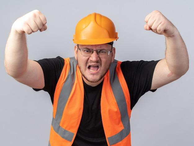 Homem construtor com colete de construção e capacete de segurança gritando com cara de raiva levantando os punhos em pé sobre o branco