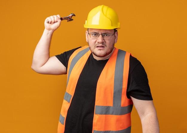 Homem construtor com colete de construção e capacete de segurança, olhando para a câmera com uma cara zangada, balançando uma chave inglesa em pé sobre a laranja