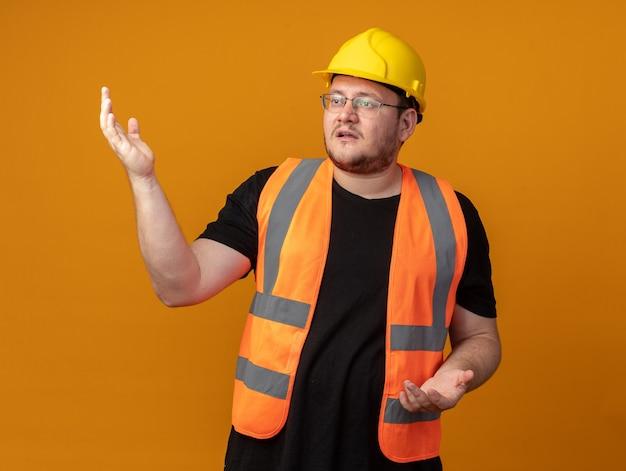 Homem construtor com colete de construção e capacete de segurança olhando para o lado confuso com os braços levantados