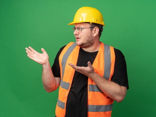 Homem construtor com colete de construção e capacete de segurança olhando para o lado, confuso, erguendo os braços indignado