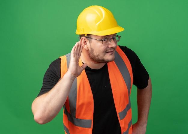 Homem construtor com colete de construção e capacete de segurança segurando a mão na orelha, tentando ouvir, parecendo intrigado