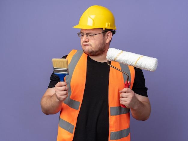 Homem construtor com colete de construção e capacete de segurança segurando o rolo de pintura e o pincel, parecendo confuso tentando fazer uma escolha em pé sobre o azul