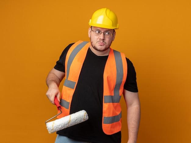 Homem construtor com colete de construção e capacete de segurança segurando o rolo de pintura, parecendo confuso