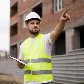 Homem construtor de tiro médio com colete