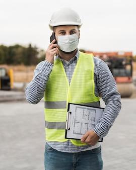 Homem construtor de vista frontal falando ao telefone