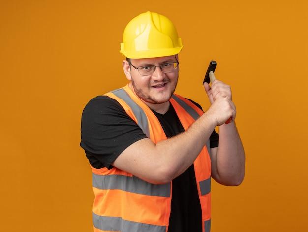 Homem construtor em colete de construção e capacete de segurança balançando um martelo parecendo zangado e louco