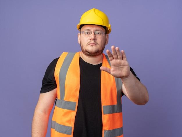 Homem construtor em colete de construção e capacete de segurança olhando para a câmera com uma cara séria, fazendo gesto de parada com a mão em pé sobre o azul