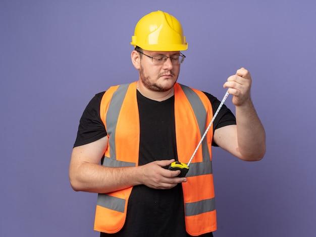 Homem construtor em colete de construção e capacete de segurança segurando fita métrica, olhando para ela com uma cara séria