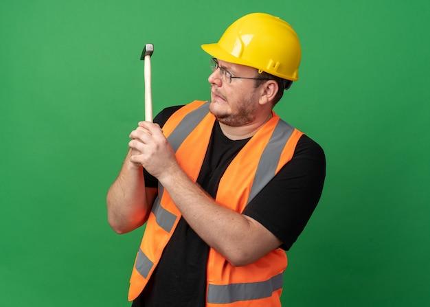 Homem construtor em colete de construção e capacete de segurança segurando um martelo olhando para ele confuso em pé sobre o verde