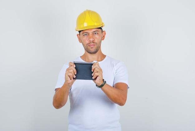 Homem construtor em t-shirt branca, capacete segurando mini notebook, vista frontal.