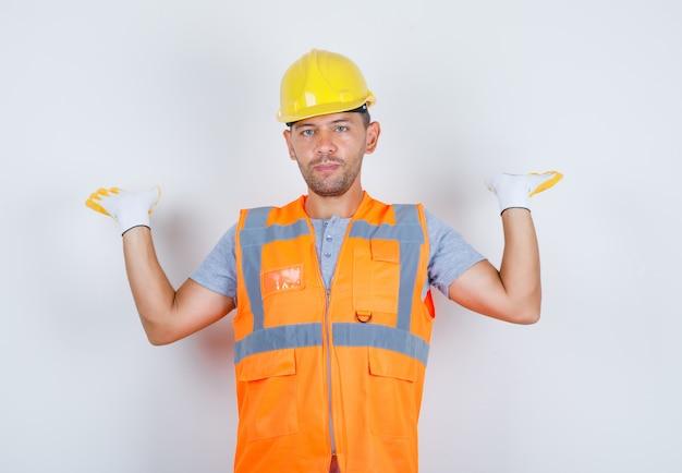 Homem construtor levantando os braços e olhando para a câmera de uniforme, capacete, luvas, vista frontal.