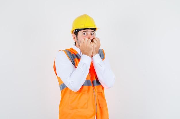 Homem construtor mordendo os punhos na camisa, uniforme e parecendo assustado, vista frontal.