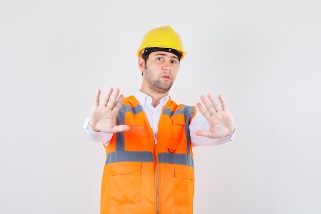 Homem construtor mostrando bastante gesto na camisa, uniforme e olhando sério. vista frontal.