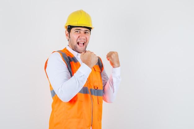 Homem construtor mostrando gesto de vencedor na camisa, uniforme e parecendo feliz. vista frontal.