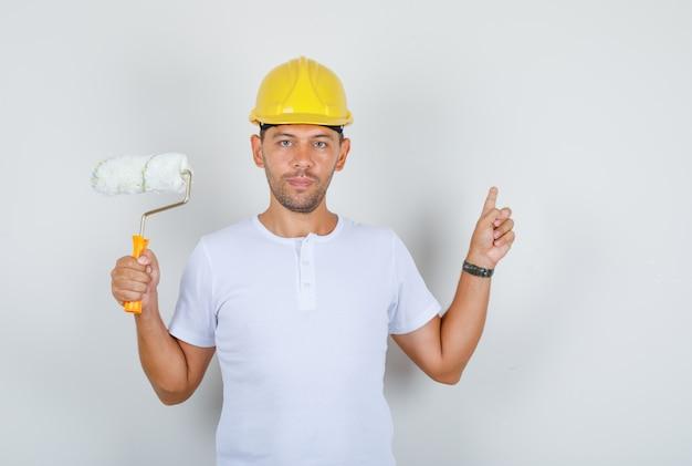 Homem construtor mostrando parede e segurando rolo de pintura em camiseta branca, capacete, vista frontal