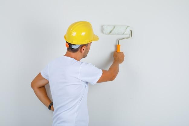Homem construtor pintando a parede com rolo em camiseta branca, capacete e olhando ocupado, vista traseira.