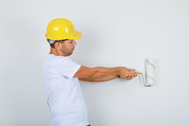 Homem construtor pintando a parede com rolo em camiseta branca, capacete e parecendo ocupado.