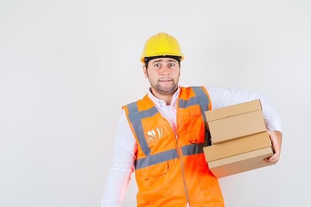 Homem construtor segurando caixas de papelão na camisa, uniforme e parecendo preocupado, vista frontal.