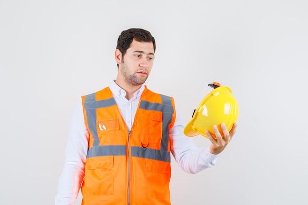 Homem construtor segurando o capacete na camisa, uniforme e olhando pensativo. vista frontal.