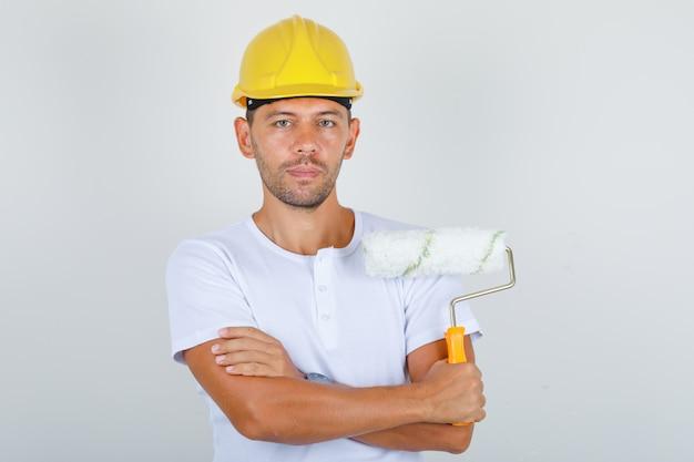 Homem construtor segurando rolo de pintura com os braços cruzados em camiseta branca, capacete, vista frontal.