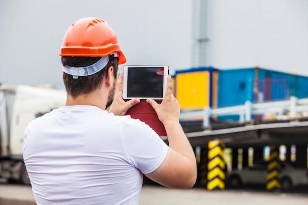 Homem construtor trabalhando com um tablet em um capacete protetor. construção, segurança, desempenho.