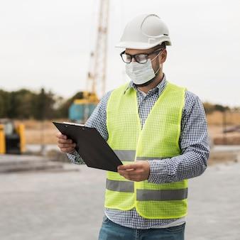 Homem construtor usando máscara de proteção