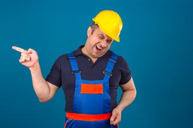 Homem construtor vestindo uniforme de construção e capacete de segurança, apontando com o dedo para alguém e rindo muito sobre parede azul isolada