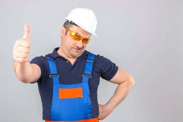 Homem construtor vestindo uniforme de construção e capacete de segurança com sorriso no rosto, piscando e mostrando os polegares para cima isolado parede branca