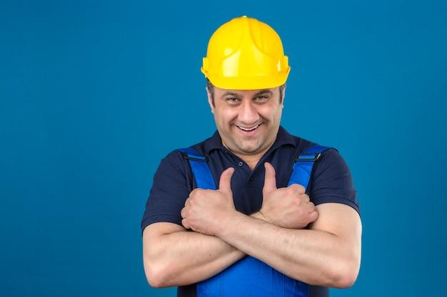 Homem construtor vestindo uniforme de construção e capacete de segurança com um grande sorriso no rosto e aparecendo os polegares sobre parede azul isolada