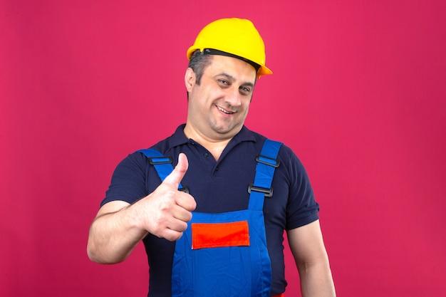 Homem construtor vestindo uniforme de construção e capacete de segurança com um grande sorriso no rosto e aparecendo os polegares sobre parede rosa isolada
