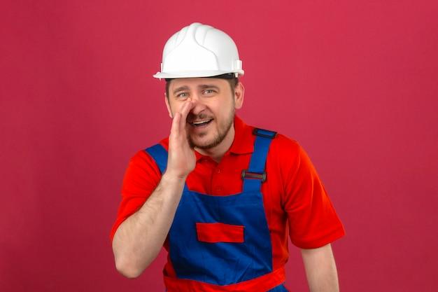 Homem construtor vestindo uniforme de construção e capacete de segurança com uma mão perto da boca dizendo um segredo em pé sobre parede rosa escura isolada