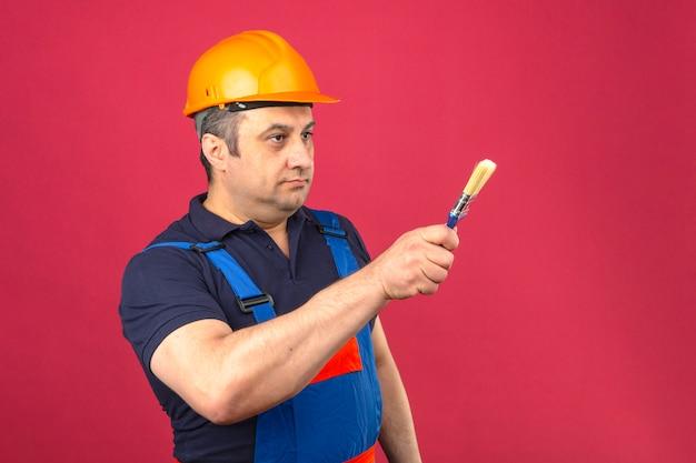 Homem construtor vestindo uniforme de construção e capacete de segurança em pé com pincel e apontando com ele para o lado ao longo da parede rosa isolada