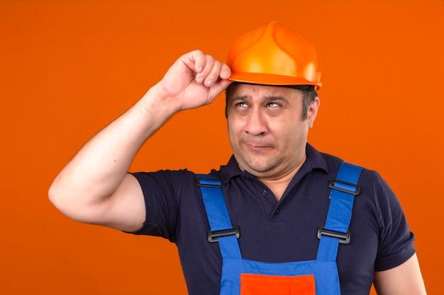Homem construtor vestindo uniforme de construção e capacete de segurança, olhando triste e decepcionado, tocando seu capacete sobre parede laranja isolada
