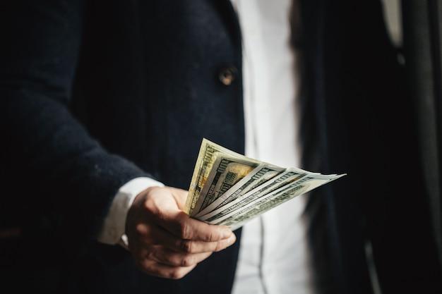 Homem contando dinheiro, homem com roupas de negócios com dólares.