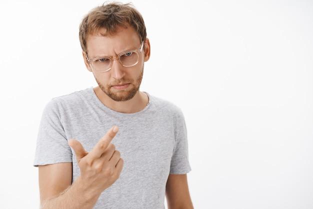 Homem contando quantas vezes o funcionário fez besteira, sentindo-se chateado e irritado querendo atirar, coitado, olhando por baixo da testa com um olhar perigoso e zangado, fazendo gesto de arma com o dedo sobre a parede branca