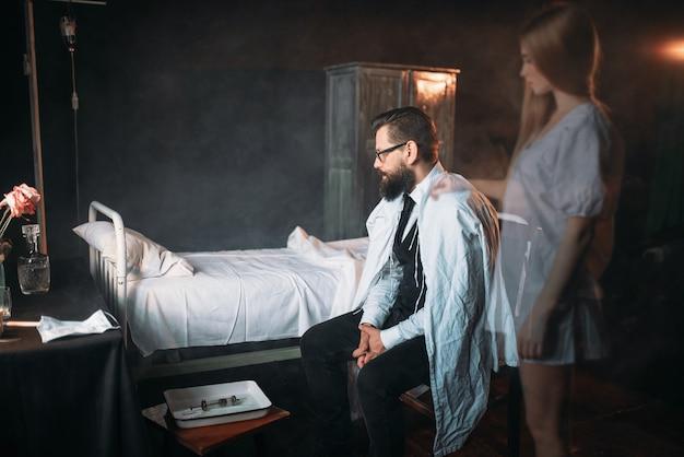 Homem contra a cama de hospital vazia, alma de mulher morta
