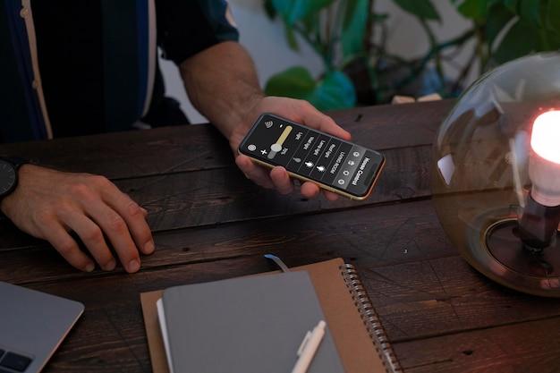 Homem controlando uma lâmpada inteligente com seu telefone