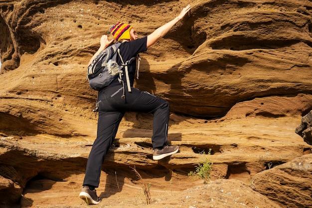 Homem corajoso com barba ruiva escalando pedra rochosa o turista de rocha sobe com uma mochila em uma camiseta preta e um chapéu engraçado feito de lã de iaque do nepal