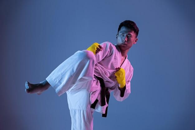 Homem coreano confiante no quimono, praticando combate corpo a corpo, artes marciais. jovem lutador do sexo masculino com faixa preta treinando na parede gradiente em luz de néon. conceito de estilo de vida saudável, esporte.
