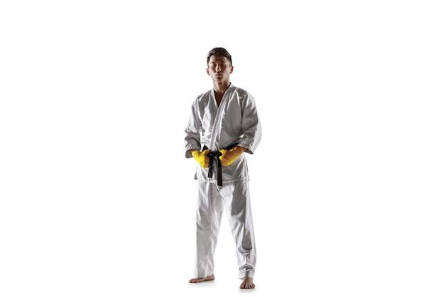 Homem coreano confiante no quimono, praticando combate corpo a corpo, artes marciais. jovem lutador masculino com treinamento de faixa preta isolado no fundo branco do estúdio. conceito de estilo de vida saudável, esporte.
