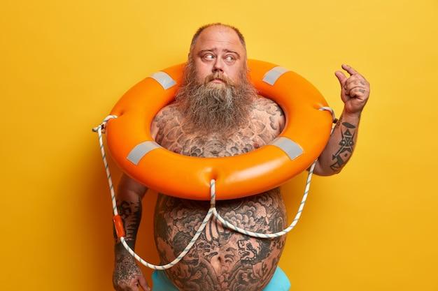 Homem corpulento descontente tem barba espessa e barriga grande, tatuagens, mostra gestos de tamanho muito pequeno, posa com bóia salva-vidas inflada, demonstra tamanho pequeno de algo, isolado na parede amarela
