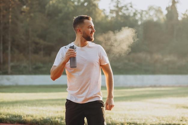 Homem corredor bebendo água no estádio