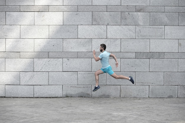 Homem correndo ao ar livre. corredor masculino saudável. se apresse. retrato de corpo inteiro de cara de fitness correndo. conquista de sucesso e excelência. atleta correndo contra a parede de concreto. o homem do esporte começa a correr.
