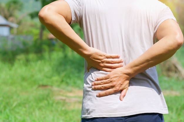 Homem correndo com dor nas costas ao ar livre
