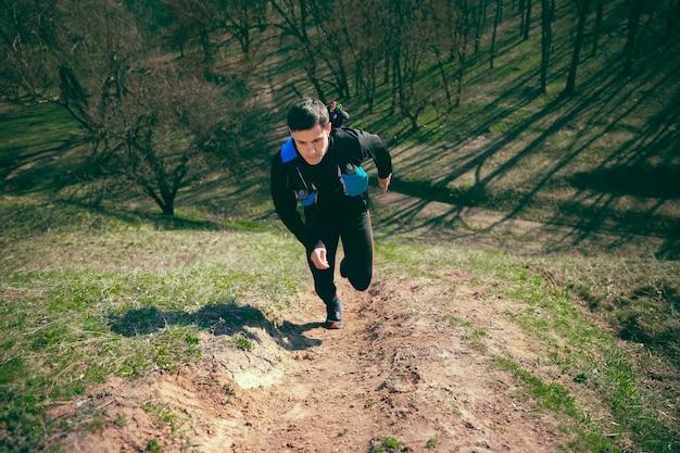 Homem correndo em um parque ou floresta contra árvores